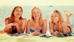 Junge Mädchen, die auf Strand liegen Stockfotografie