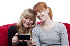 Junge Mädchen, die etwas auf Handy zeigen Stockfotos
