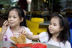 Junge Mädchen, die gebratenes Huhn essen Stockbilder