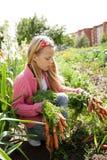 Junge Mädchen, die im Gemüsegarten arbeiten Stockfotos