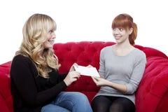 Junge Mädchen geben ein Zeichen auf rotem Sofa Lizenzfreies Stockfoto