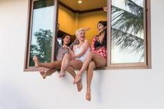 Junge Mädchen-Gruppe, die auf dem sprechenden Fensterbrett, Schönheits-Freund-Kommunikation sitzt lizenzfreie stockbilder
