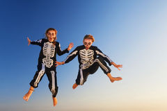 Junge Mädchen in Halloween-Kostümen springen hoch mit Spaß Stockfoto
