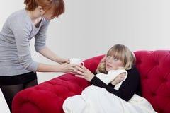 Junge Mädchen hat Fieber und erhält einen Tee Stockfotos