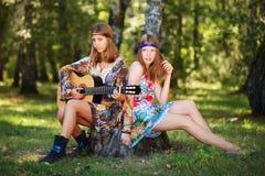 Junge Mädchen mit der Gitarre, die in einem Wald sich entspannt Stockbild