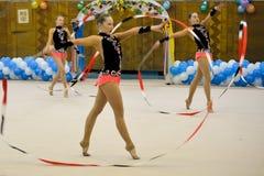 Junge Mädchen nehmen an einem Gymnastikwettbewerb teil Lizenzfreie Stockbilder