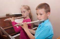 Junge, Mädchen und Flöte Stockbilder