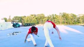 Junge Männer capoeira Kämpfer in den roten und weißen Showtricks stock footage