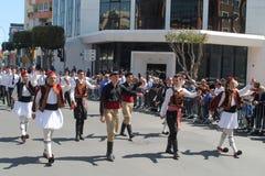 Junge Männer in den nationalen Kostümen teilnehmend an der Parade lizenzfreie stockbilder
