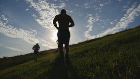 Junge Männer, die über grünen Hügel über Hintergrund des blauen Himmels laufen Männliche Athleten rüttelt in der Natur bei Sonnen stock video footage