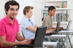 Junge Männer, die an Computern arbeiten Stockbild