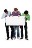 Junge Männer, die ein unbelegtes Zeichen halten lizenzfreies stockfoto
