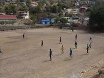 Junge Männer, die ein zufälliges Spiel des Fußballs auf einem trockenen Feld in den Tropen spielen stock video footage
