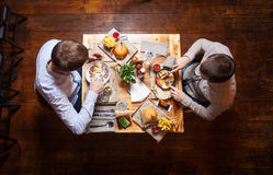Junge Männer, die an einem Café zu Mittag essen Stockfotos