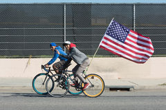 Junge Männer, die Fahrrad hält amerikanische Flagge fahren Lizenzfreie Stockbilder
