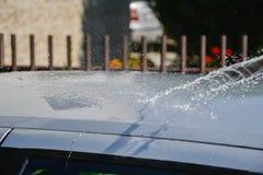 Junge Männer, die silbernes Auto mit Druckwasser und Bürste am sonnigen Tag waschen Schließen Sie oben vom Reinigungsauto auf Som lizenzfreies stockbild