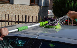 Junge Männer, die silbernes Auto mit Druckwasser und Bürste am sonnigen Tag waschen Schließen Sie oben vom Reinigungsauto auf Som Stockbilder