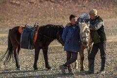 Junge Männer Eagle Hunters, der nahe ihren Pferden während der Jagd in der Gebirgs-Wüste von West-Mongolei steht Stockfotos