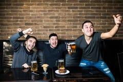 Junge Männer trinken Bier, essen snaks und das Zujubeln für Fußball Gewinnende Gefühle stockbild