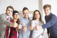 Junge Männer und Frauen, die sich Daumen zeigen Stockfoto
