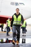 Junge männliche Arbeitskraft, die auf nasse Rollbahn am Flughafen geht Lizenzfreie Stockfotografie