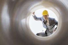Junge männliche Aufsichtskraft, die großes Rohr an der Baustelle überprüft Lizenzfreie Stockbilder