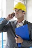 Junge männliche Aufsichtskraft mit Klemmbrett unter Verwendung des Handys in der Industrie Lizenzfreies Stockbild