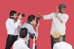 Junge männliche Berühmtheit, die Gesicht von den Fotografen über rotem Hintergrund abschirmt Lizenzfreie Stockfotografie