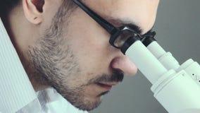 Junge männliche Doktorbetrachtung durch Mikroskop stock footage