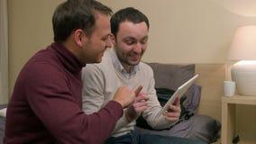 Junge männliche Freunde und Sitzen auf dem Sofa und Anwendung der Tablette, etwas und das Lachen duscussing stock footage