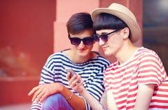 Junge männliche Paare, die auf tragbarem Gerät plaudern stockbild