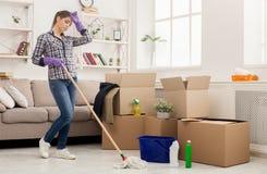 Junge müde Frau, die neues Haus mit Mopp säubert stockfoto