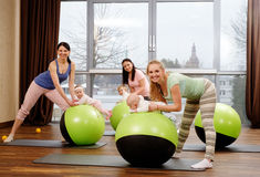 Junge Mütter und ihre Babys, die Yogaübungen auf Wolldecken am Eignungsstudio tun Stockfoto