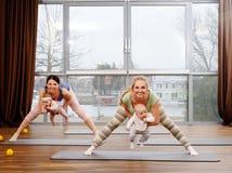 Junge Mütter und ihre Babys, die Yogaübungen auf Wolldecken am Eignungsstudio tun Stockbilder