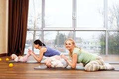 Junge Mütter und ihre Babys, die Yogaübungen auf Wolldecken am Eignungsstudio tun Stockbild