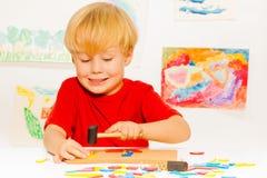 Junge machen Bild mit Hammernägeln und -blöcken Stockfoto