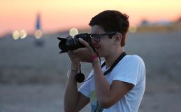 Junge macht ein Foto mit der Kamera bei Sonnenuntergang auf dem Strand Stockfotografie