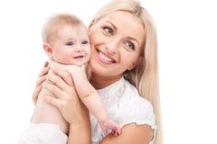 Junge Mama, die kleines Baby umarmt schönes blondes haltenes Baby und Lächeln Stockbild