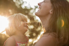 Junge Mama, die sein blondes Tochtermädchen auf seinen Armen und dem Lachen oder dem Lächeln hält Warme Sonnenuntergangleuchte Fa Lizenzfreie Stockbilder