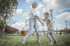 Junge Mama, die sich herum, wirbelnd mit ihrem Sohn am Park dreht Gl?ckliches Familienkonzept stockfoto