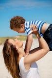 Junge Mamma, die ihren Sohn trägt Lizenzfreie Stockfotografie