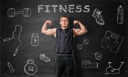 Junge Mann der mit Muskeln, der seine Bizepsmuskeln auf dem Hintergrund der Tafel mit Eignung zeigt, kritzelt stockbild
