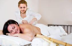 Junge Masseuse tut gesunde Massage der Rückseite und der Lende Erwachsenen an Stockfotografie