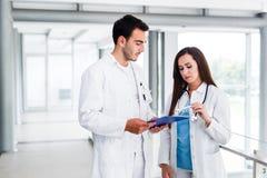 Junge medizinische Kollegen, die Daten bezüglich der Pappe analysieren Lizenzfreies Stockbild