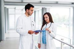 Junge medizinische Kollegen, die Daten bezüglich der Pappe analysieren Stockfoto
