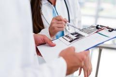 Junge medizinische Kollegen, die Daten bezüglich der Pappe analysieren Lizenzfreie Stockbilder