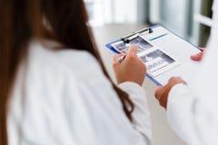 Junge medizinische Kollegen, die Daten bezüglich der Pappe analysieren Lizenzfreie Stockfotos