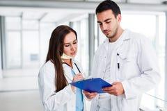 Junge medizinische Kollegen, die Daten bezüglich der Pappe analysieren Stockbilder