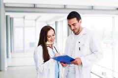 Junge medizinische Kollegen, die Daten bezüglich der Pappe analysieren Lizenzfreie Stockfotografie