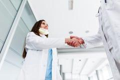 Junge medizinische Kollegen rütteln Hände Lizenzfreie Stockbilder